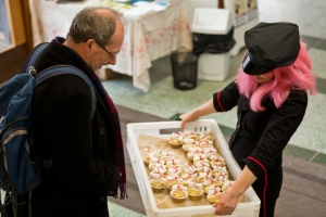 Sally (in pink wig and Postie hat) delivers some poem-cakes)/Chris Scott